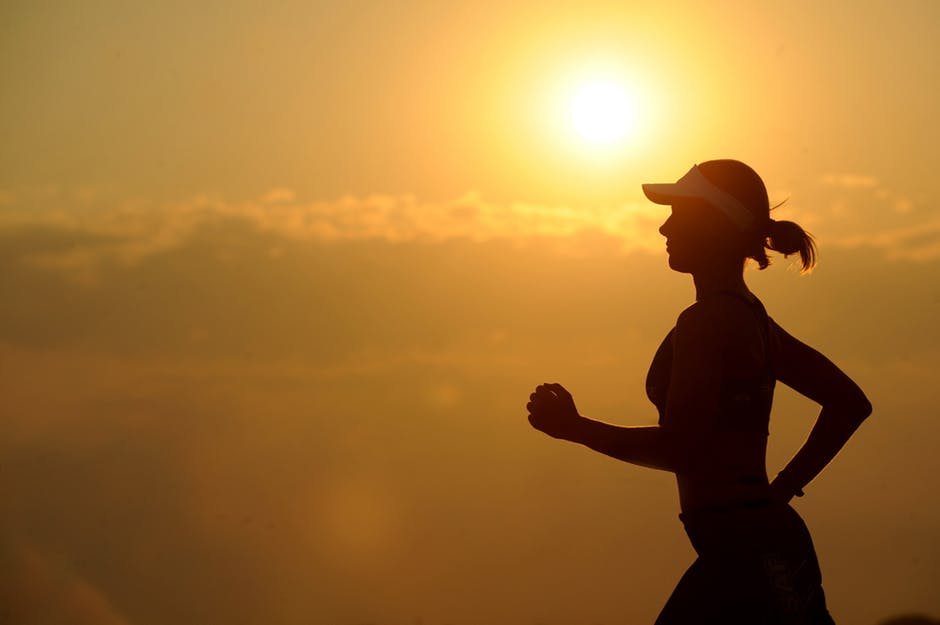 woman running with sunset in the distance